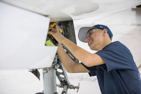 Aviation student working on plane.